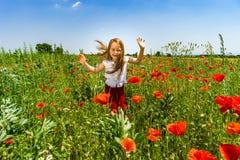 Милая маленькая девочка играя в красных маках field летний день, красота Стоковое Фото
