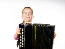 Милая маленькая девочка играя губную гармонику, концепцию образования музыки стоковая фотография rf