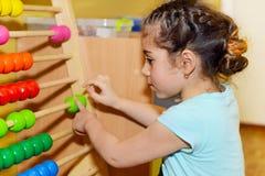 Милая маленькая девочка играя с абакусом стоковое фото rf