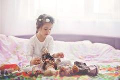 Милая маленькая девочка, играя с куклами в кровати дома Стоковое фото RF