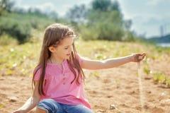 Милая маленькая девочка играя с песком в парке стоковая фотография