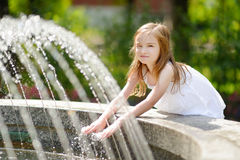 Милая маленькая девочка играя с фонтаном города на горячий летний день Стоковые Изображения