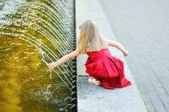 Милая маленькая девочка играя с фонтаном города на горячий и солнечный летний день Стоковая Фотография RF