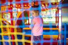 Милая маленькая девочка имеет потеху на мягкой внешней спортивной площадке Стоковые Фотографии RF