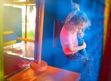 Милая маленькая девочка имеет потеху на мягкой внешней спортивной площадке Стоковая Фотография RF