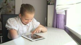 Милая маленькая девочка использует цифровой планшет видеоматериал