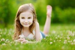 Милая маленькая девочка кладя в траву стоковые фото