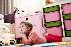 Милая маленькая девочка мечтая лежать на поле в ` s r детей стоковые фото