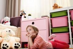 Милая маленькая девочка мечтая лежать на поле в ` s r детей Стоковая Фотография RF