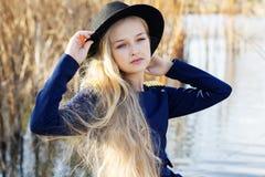 Милая маленькая девочка моды отдыхает около озера стоковая фотография