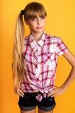Милая маленькая девочка на желтой предпосылке Стоковая Фотография