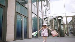 Милая маленькая девочка на покупках портрет ребенк с хозяйственными сумками Шоппинг девушка сток-видео