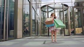 Милая маленькая девочка на покупках портрет ребенк с хозяйственными сумками Шоппинг девушка видеоматериал