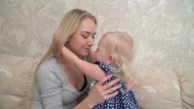 Милая маленькая девочка обнимает ее мать сток-видео