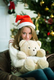 Милая маленькая девочка обнимает плюшевый медвежонка в Рожденственской ночи Стоковая Фотография RF