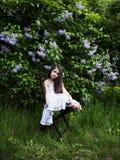милая маленькая девочка, одетая в белом платье, сидя в саде в парке Стоковое фото RF
