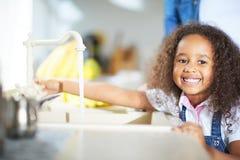Милая маленькая девочка поворачивая дальше кран Стоковая Фотография