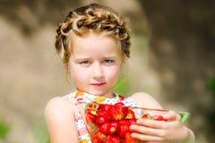 Милая маленькая девочка представляя с свежей красной клубникой в солнечном g стоковое фото rf