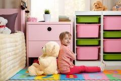 Милая маленькая девочка при большой плюшевый медвежонок сидя на поле в стоковые фото