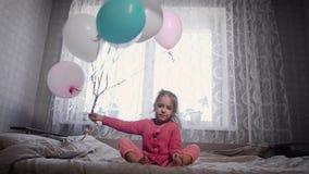Милая маленькая девочка при светлые волосы, одетые в розовых пижамах сидя на кровати родителей, и развевая с боку на бок сток-видео