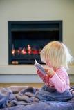 Милая маленькая девочка при тетрадь сидя под предпосылкой крышки и камина Стоковые Изображения