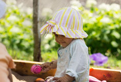 Милая маленькая девочка сидя в песке пока играющ Стоковое Изображение