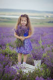 Милая маленькая девочка сидя в поле лаванды в славном лодочнике шляпы с фиолетовым цветком на ем стоковая фотография rf