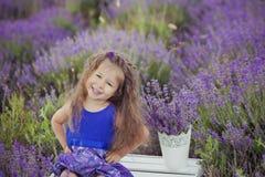 Милая маленькая девочка сидя в поле лаванды в славном лодочнике шляпы с фиолетовым цветком на ем стоковое фото