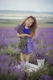 Милая маленькая девочка сидя в поле лаванды в славном лодочнике шляпы с фиолетовым цветком на ем стоковые фотографии rf