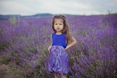 Милая маленькая девочка сидя в поле лаванды в славном лодочнике шляпы с фиолетовым цветком на ем стоковое изображение