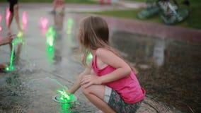 Милая маленькая девочка сидя на корточках и играя с покрашенными струями воды на фонтане в горячем летнем дне видеоматериал