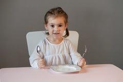 Милая маленькая девочка сидя на таблице с плитой, держащ вилку и ложку Стоковая Фотография