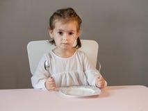 Милая маленькая девочка сидя на таблице с плитой, держащ вилку и ложку Стоковые Фотографии RF
