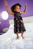 Милая маленькая девочка скача на кровать родителя Стоковые Изображения