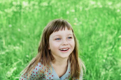 Милая маленькая девочка смеясь над на зеленом луге внешнем, счастливая концепция детства стоковое изображение
