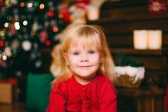 Милая маленькая девочка смотря в камеру над предпосылкой с стоковая фотография