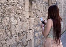 Милая маленькая девочка смотря телефон Стоковые Изображения RF