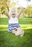 Милая маленькая девочка с большими пальцами руки вверх в траве Стоковое Изображение