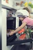 Милая маленькая девочка с ее печеньями выпечки матери в печи стоковое изображение rf
