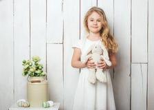 Милая маленькая девочка с игрушкой кролика зайчика на белой деревянной предпосылке Стоковое Фото