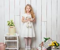 Милая маленькая девочка с игрушкой кролика зайчика на белой деревянной предпосылке Стоковое Изображение RF