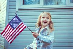 Милая маленькая девочка с длинными курчавыми светлыми волосами усмехаясь и развевая Стоковые Изображения RF