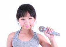 Милая маленькая девочка с микрофоном в ее руке Стоковые Фотографии RF