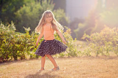 Милая маленькая девочка с юбкой, танцами и завихряться вокруг, лето Стоковая Фотография