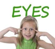 Милая маленькая девочка указывая она глаза в частях тела уча школу Стоковые Фотографии RF