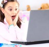 Милая маленькая девочка усмехаясь и смотря компьтер-книжку Стоковое Фото