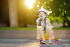 Милая маленькая девочка уча к скейтборду на красивый летний день в парке Ребенок наслаждаясь skateboarding ездой outdoors Стоковые Изображения RF