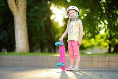 Милая маленькая девочка уча к скейтборду на красивый летний день в парке Ребенок наслаждаясь skateboarding ездой outdoors Стоковое Изображение