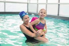Милая маленькая девочка уча поплавать с тренером Стоковые Изображения RF