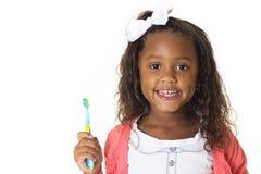 Милая маленькая девочка чистя ее зубы щеткой Стоковые Изображения